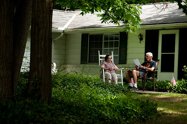 An eldery couple sitting in chairs outside and having a conversation.