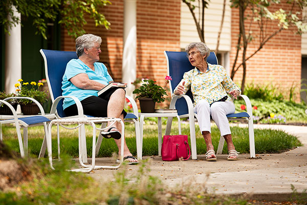 Two elderly women sitting outside in chairs conversing.