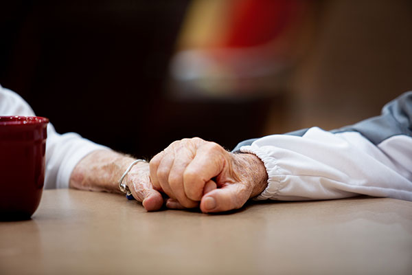 An elderly man and woman's hands clasping.