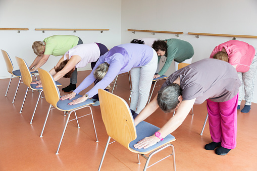 senior women exercising yoga and pilates using chairs, doing the downward facing dog position,