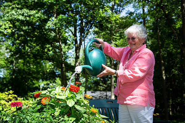 An older woman watering her flowers while smiling.