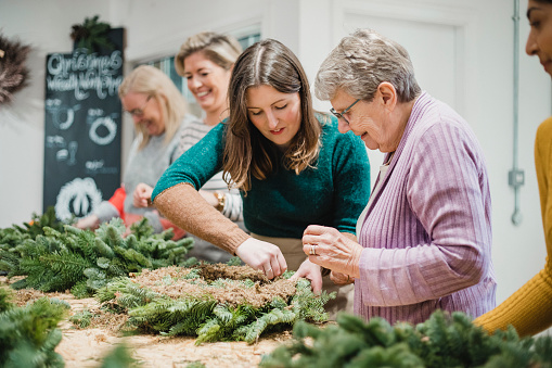 Senior woman is getting assistance from the florist at her Christmas wreath-making workshop.