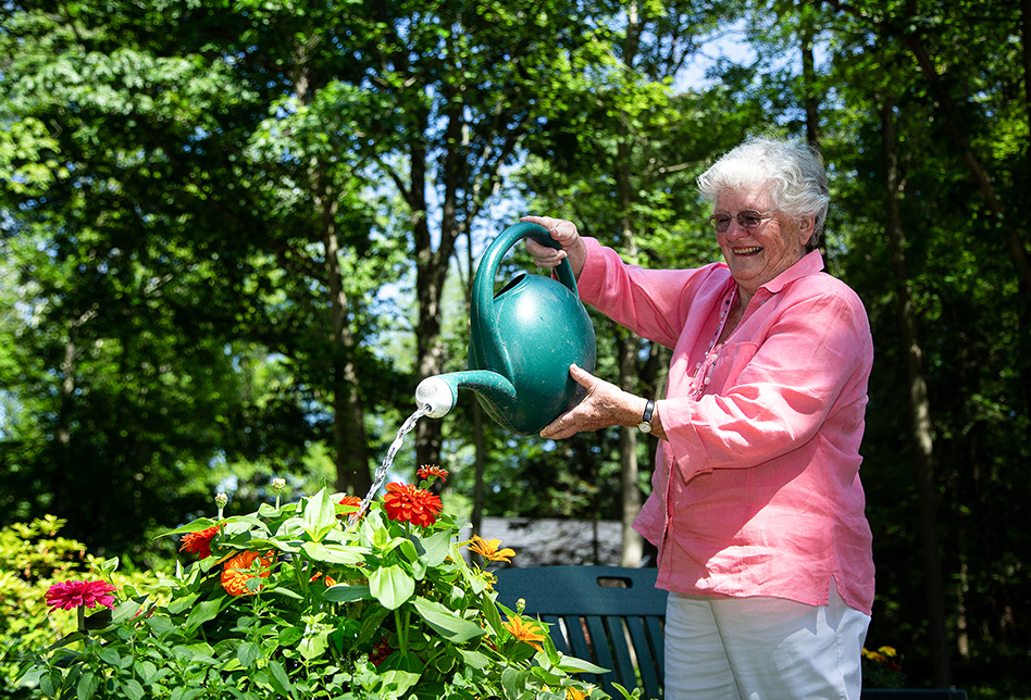 An elderly woman watering flowers outside while smiling.