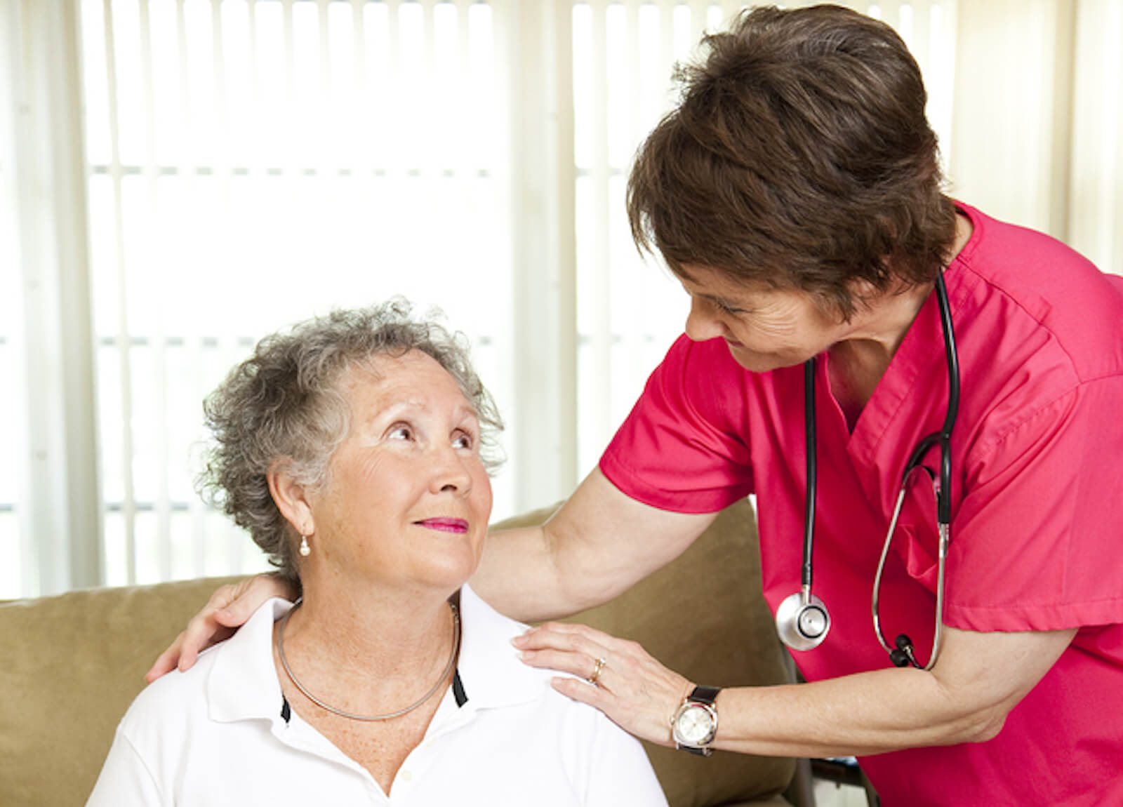 A nurse helps a senior woman at an assisted living facility