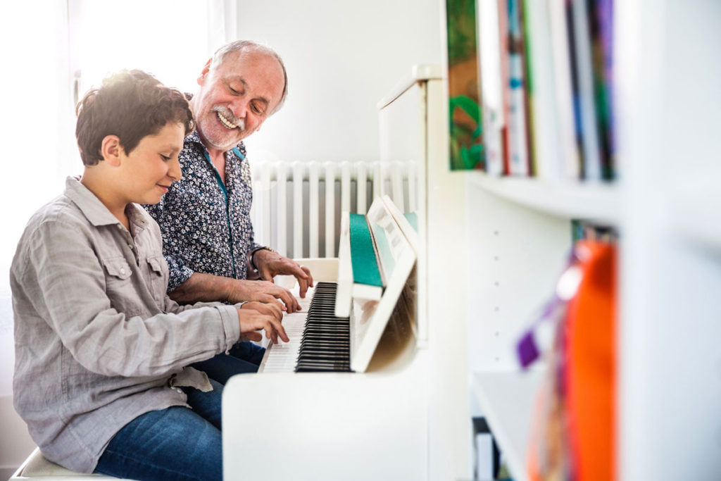 A senior man and his grandson playing the piano together on a white piano