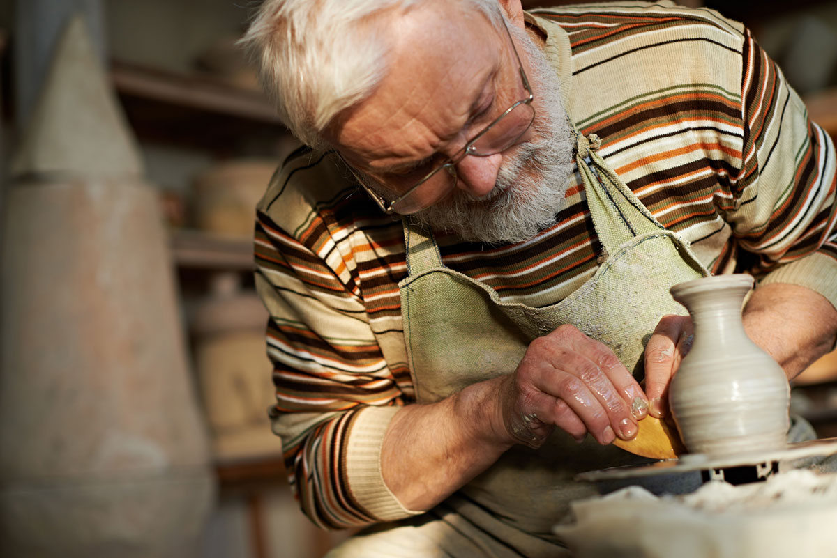 A senior man works on crafting a vase from clay on a potter's wheel