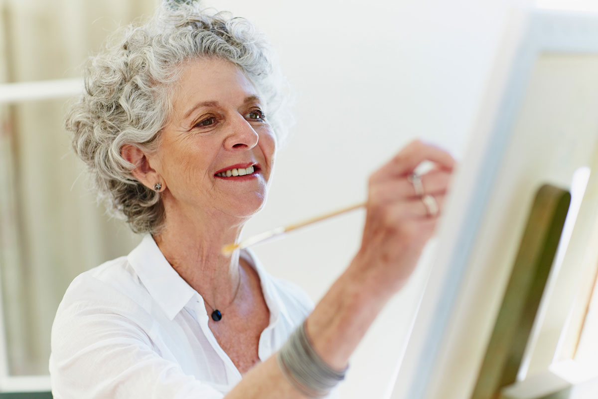 A senior woman smiling and painting on a canvas