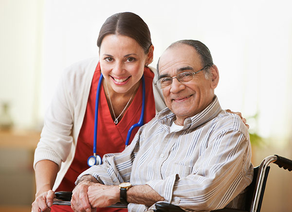 A nurse with an elderly man in a wheel chair smiling at the camera.