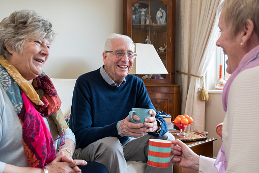 Group of senior friends meeting at home for coffee