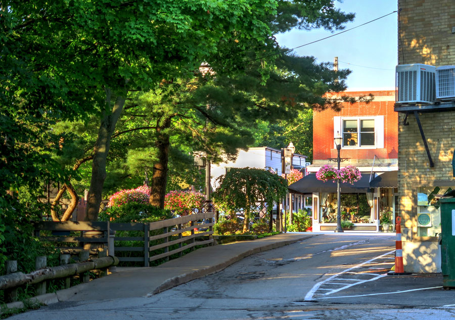 A photo of a street by the park in the downtown shopping area of Chagrin Falls