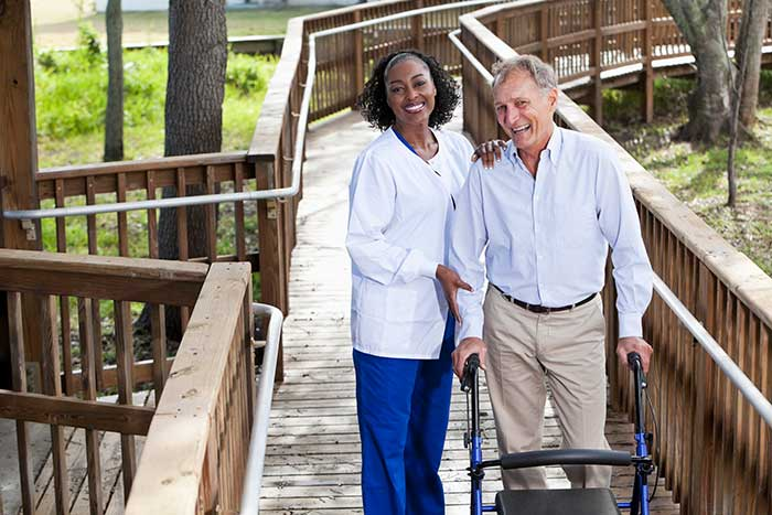 A senior man with a walker goes on a walk on a boardwalk with the assistance of a health care professional