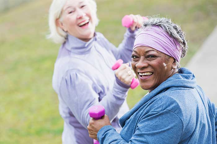 Two senior women lifting small weights and exercising outdoors